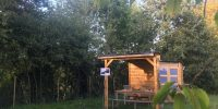 Cabane avec auvent avec table et banc pour profiter d'un barbecue au milieu de la nature.